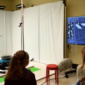 Model student stands in front of white screens of Motion Capture Studio