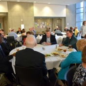 Chemistry faculty and staff seated around a table with the Otienos.