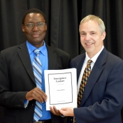 Tom Otieno and Richard Byrd pose with sheet music for commissioned musical piece