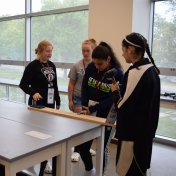 Students clamp board to desk for an earthquake activity