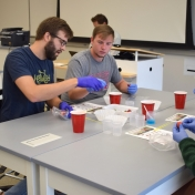 Model students smash strawberries for a lab experiment