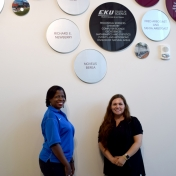 Monica Johnson and Tammy Peyton from Novelis stand in front of recognition wall